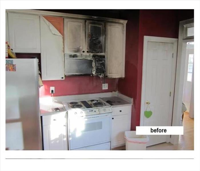 Kitchen fire with damage to cabinets and microwave